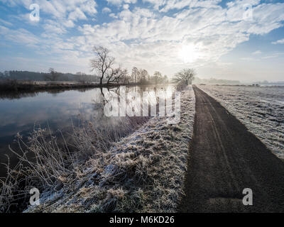 River Aller on a frozen winter day, hiking and cycling path along the river, between Celle and Altencelle, Germany - Stock Photo