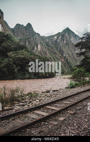 Old railways tracks running alongside the Urubamba River, a popular route for those walking to Machu Picchu - Stock Photo