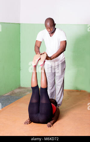 The gym coach trains the legs of the young woman lying in front of him. - Stock Photo