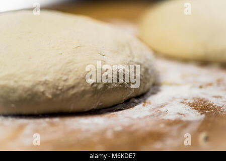 horizontal image of two rounds of rustic, crusty hearty bread rising on flour covered wooden board. selective focus - Stock Photo