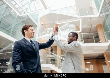 young colleagues giving each other high five while standing in an office