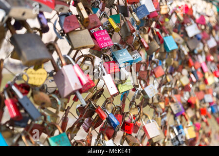 Colorful locked love locks on a bridge in Salzburg Austria. Lovers throuw away the key to express their love. Shallow - Stock Photo