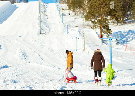 Family walking in ski resort - Stock Photo