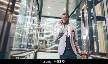 afroamerican businessman in modern glass elevator talking on phone - Stock Photo