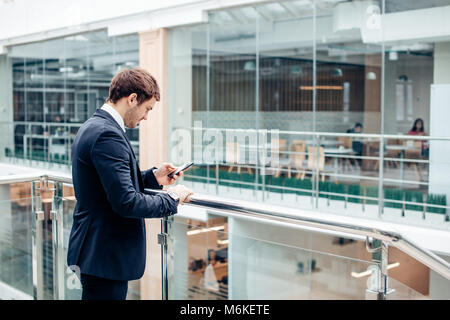 businessman with smartphone over office building