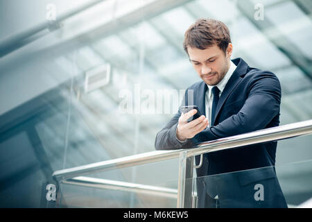 businessman with smartphone over office building - Stock Photo