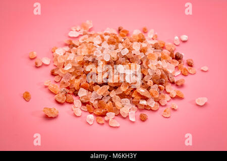 coarse crystals of pink  Himalayan salt, a pile on pink background, top view - Stock Photo