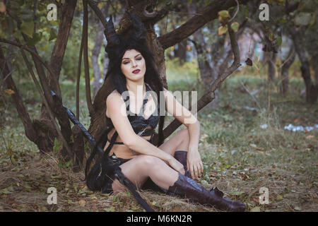 Beautiful woman from the tribe sits under a tree - Stock Photo