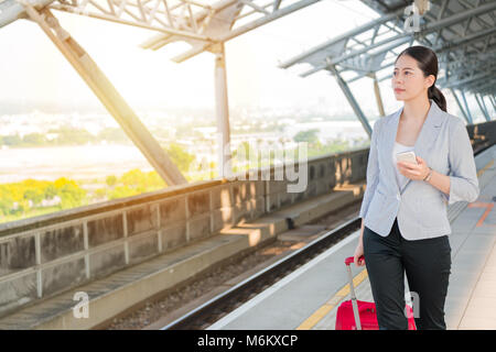 Asian business woman walking on the rail platform and holding her suitcase luggage for her travel journey. - Stock Photo
