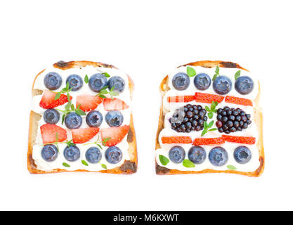 Slices  of bread with cream cheese berries and thyme isolated on white - Stock Photo
