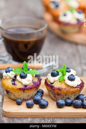 fresh  muffins with blueberry and cup of coffee on wooden background - Stock Photo