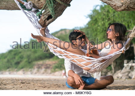 couple lover enjoy honeymoon and long vacation on the sea beach, siiting on the swing together relax and confortable, - Stock Photo