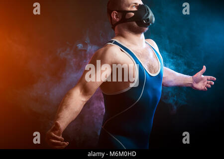 A strong dark-haired sportman  in a blue wrestling tights and training mask posing  against a blue and red vape - Stock Photo