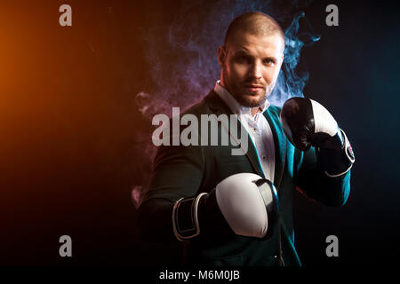 Young handsome businessman man in white shirt, green jacket, black and white boxing gloves smiling and ready to - Stock Photo