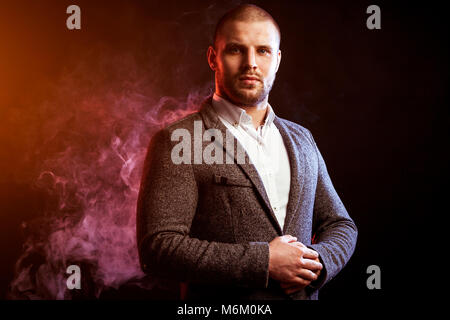 Young handsome man manager in white shirt and  gray suit posing against red smoke from a vape  on black isolated - Stock Photo