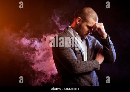 Young handsome man manager in white shirt and  gray suit standing and thinking against red smoke from a vape  on - Stock Photo