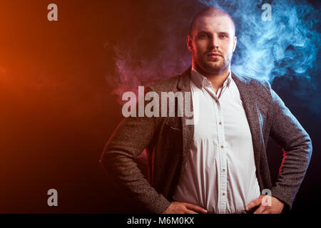 Young intelligent man businessman in white shirt and gray suit looks closely and posing against a red smoke background - Stock Photo