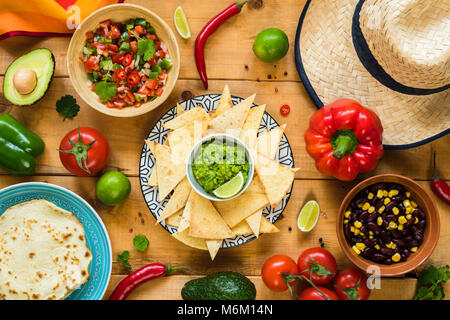 Traditional Mexican food on wooden table. Tortilla chips, guacamole, nachos, beans and salsa. Table top view - Stock Photo