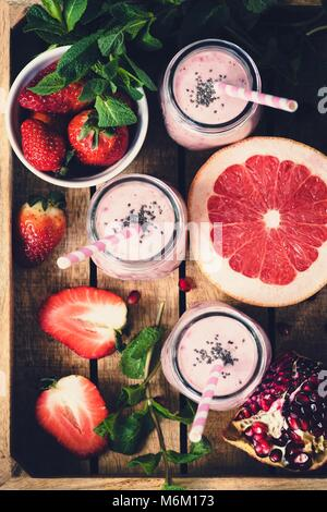 Pink fresh smoothies with grapefruit, strawberry and pomegranate in wooden tray, top view, selective focus, toned - Stock Photo