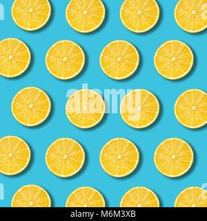 Lemon slices pattern on vibrant turquoise color background. Minimal flat lay food texture - Stock Photo