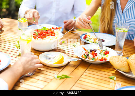 Family dinner variety of Italian dishes on wooden table in the garden. Close up - Stock Photo
