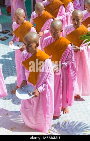 Nuns lined up holding plates queuing for food at Thetkya Thidar Nunnery, Sakyadhita Thilashin Nunnery School, Sagaing, - Stock Photo