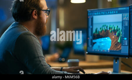 Male Game Developer Works on a New Level Design. He's Handsome Bearded Man with Glasses and Works in a Creative Office with other Talented People.