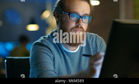 Talented Young Concept Artist Drawing on a Digital Pen Display Tablet While Sitting at His Working Place in Modern - Stock Photo