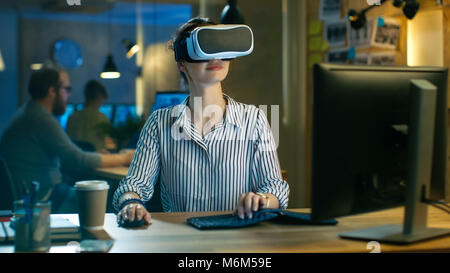 Beautiful Female Virtual Reality Engineer/ Developer Wearing VR Headset Creates Content. She Works in a Creative - Stock Photo