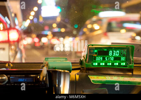 The digital taxi meter on the dashboard of cab shows kilometer and cost. Night taxi ride in traffic jam. - Stock Photo