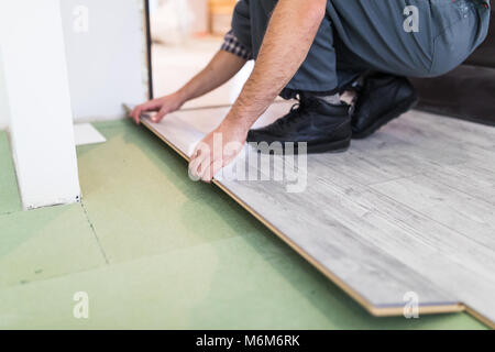 Close up man hands worker installing laminate flooring in the new room - Stock Photo