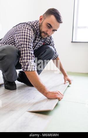 Man work laying laminate flooring at home - Stock Photo