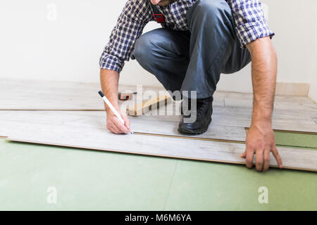 Close up man hands worker installing laminate flooring in the room - Stock Photo
