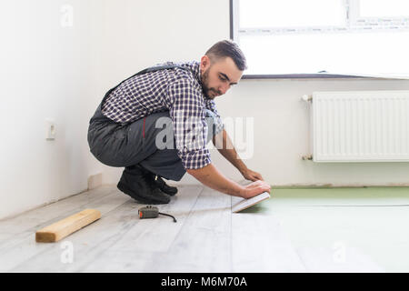 man is repairing the floor in the house, laminate flooring in the style of old boards - Stock Photo