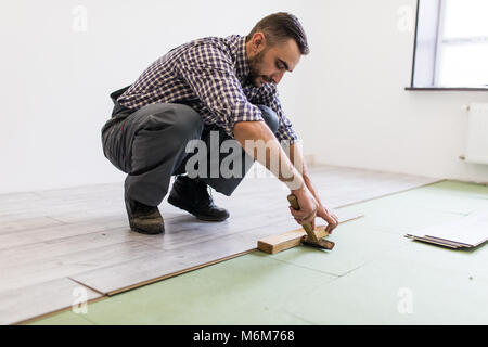 Man laying laminate flooring in construction concept - Stock Photo