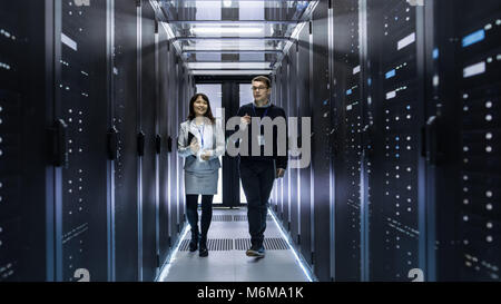 Caucasian Male and Asian Female IT Technicians Walking through Corridor of Data Center with Rows of Rack Servers. - Stock Photo