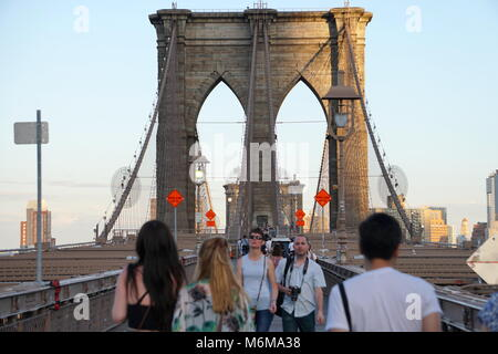 New York City, NY - June 7, 2016: Tourists walk across the famous Brooklyn Bridge at sunset on a summer evening - Stock Photo