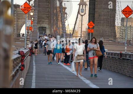 New York City, NY - June 7, 2016: Tourists visiting Manhattan walk across the Brooklyn Bridge at sunset amoung busy - Stock Photo