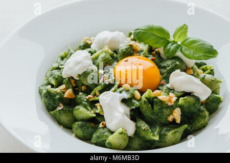 tasty fresh green conchiglie with spinach on white plate - Stock Photo