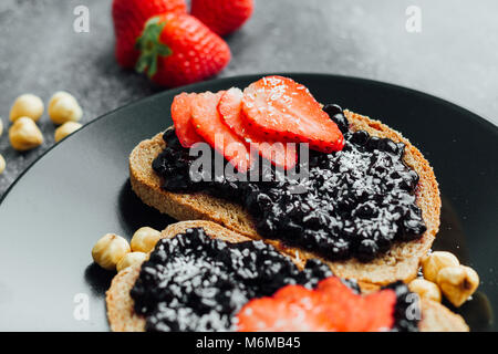 blueberry jam on bread with sliced strawberry - Stock Photo