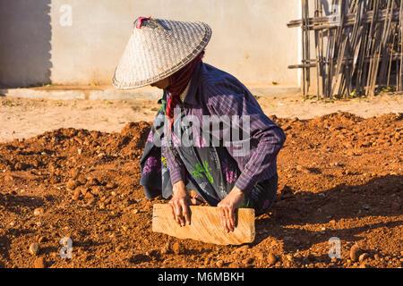 Villagers undertake manual road construction work at West Phwar Saw Village, Bagan, Myanmar (Burma), Asia - woman - Stock Photo