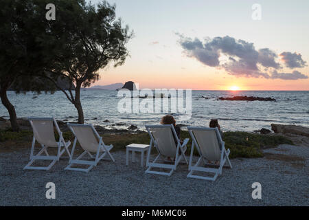 Deckchairs looking over the sunset at Nefeli Sunset Studios, Pollonia, Milos, Cyclades, Aegean Sea, Greek Islands; - Stock Photo