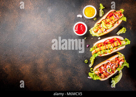 Assortment of different homemade hot dogs with sausage, fried onion, tomatoes and beans, dark rusty background copy - Stock Photo