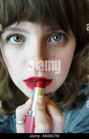 Young woman applying makeup herself - Stock Photo