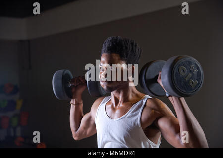 African athlete lifting weights in gym - Stock Photo