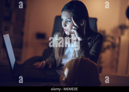 Worried lonely young woman looking at lighted screen of a laptop in night at the home. She is tired because working - Stock Photo