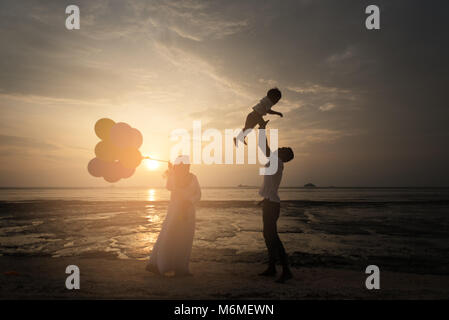sillhouette of happy asian family having fun time at the beach with sunset view as background. family concept