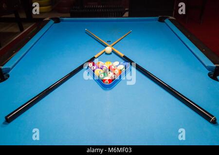 Billiards balls and cue on billiards table - Stock Photo