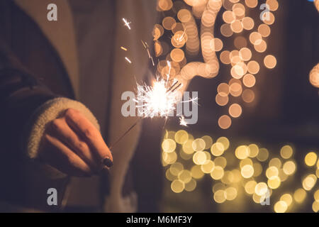 Close up of female hand holding sparkler against bokeh background. Space for copy. - Stock Photo