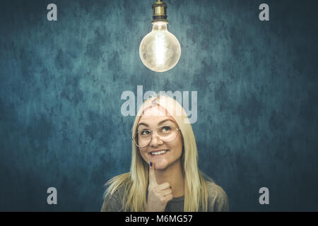 Happy thoughtful woman with light bulb above head isolated on blue wall background. Thinking and idea concepts. - Stock Photo